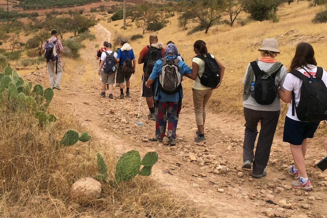 A group of blind and sighted travellers walking through open Moroccan countryside