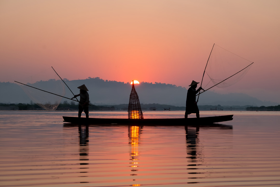 Two fisherman balance precariously on opposite ends of a wooden boat during sunset