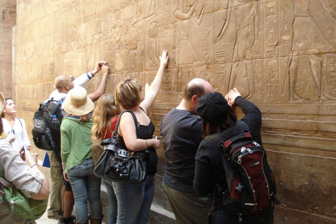 A group of travellers feel the ancient carvings