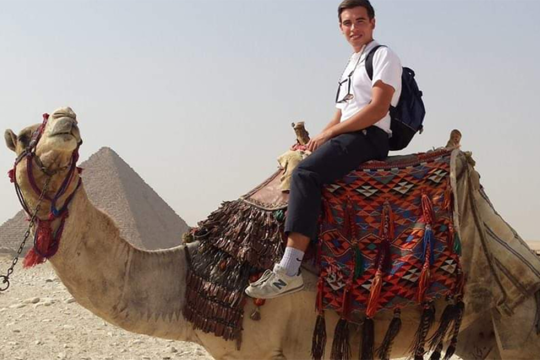 A young man riding a camel around the pyramids