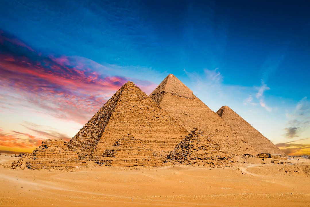 A cluster of pyramids of varying sizes against a vivid blue and pink sky