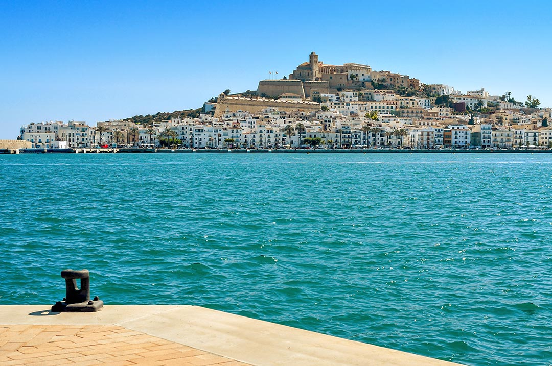 Turquoise sea and an empty mooring and the Mediterranean Sea, with Sa Penya and Dalt Vila districts, the old town of Ibiza Town, in the background, in the Balearic Islands, Spain