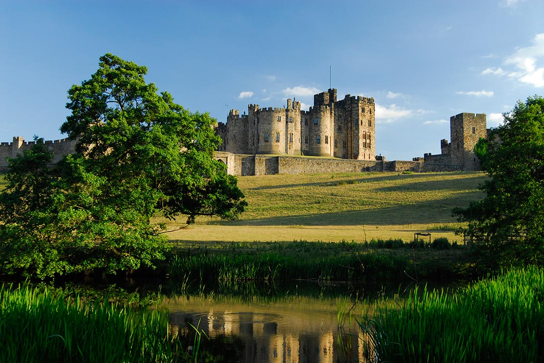 A view of Alnwick Castle across the fields, on a bright summers day