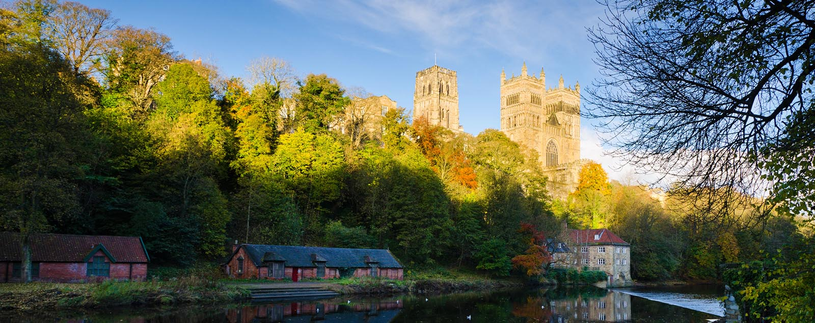 A view of Durham across still waters, the cities beautiful architecture reflected on the water.