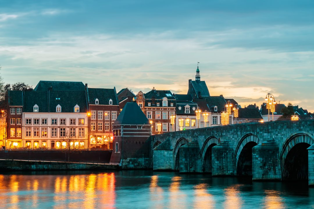 View at the famous Dutch Sint Servaas bridge with twilight lights in the city center of Maastricht