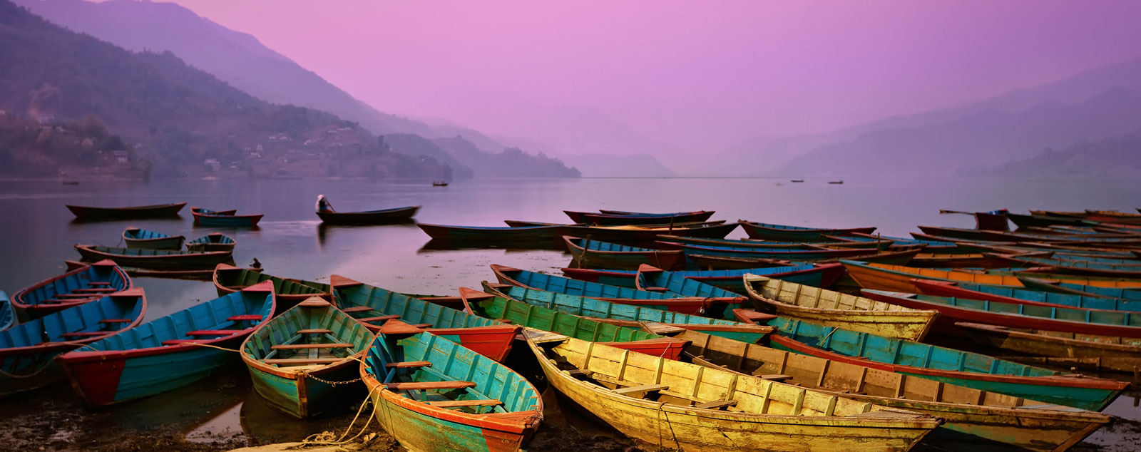 Yellow and green boats on Lake Phewa with purple haze in background,