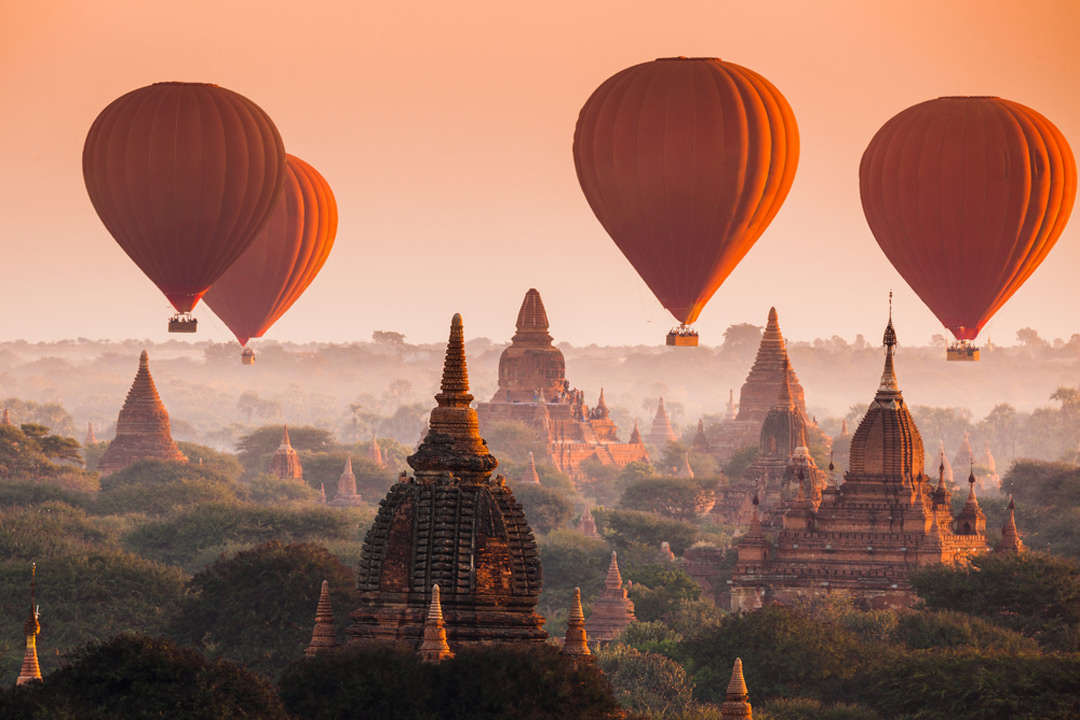 Orange balloons flying above temples at dawn