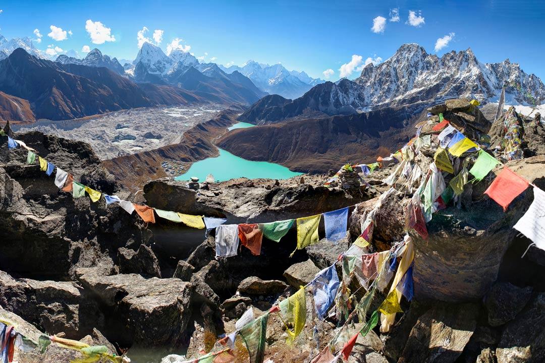 View of blue lake in Nepal surrounded by mountains and with prayer flags in the front
