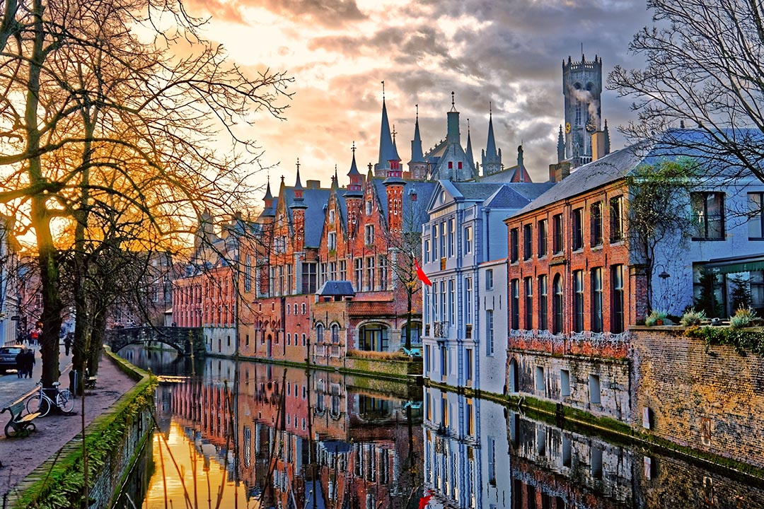Canals of Bruges with buildings of different colours in the background.