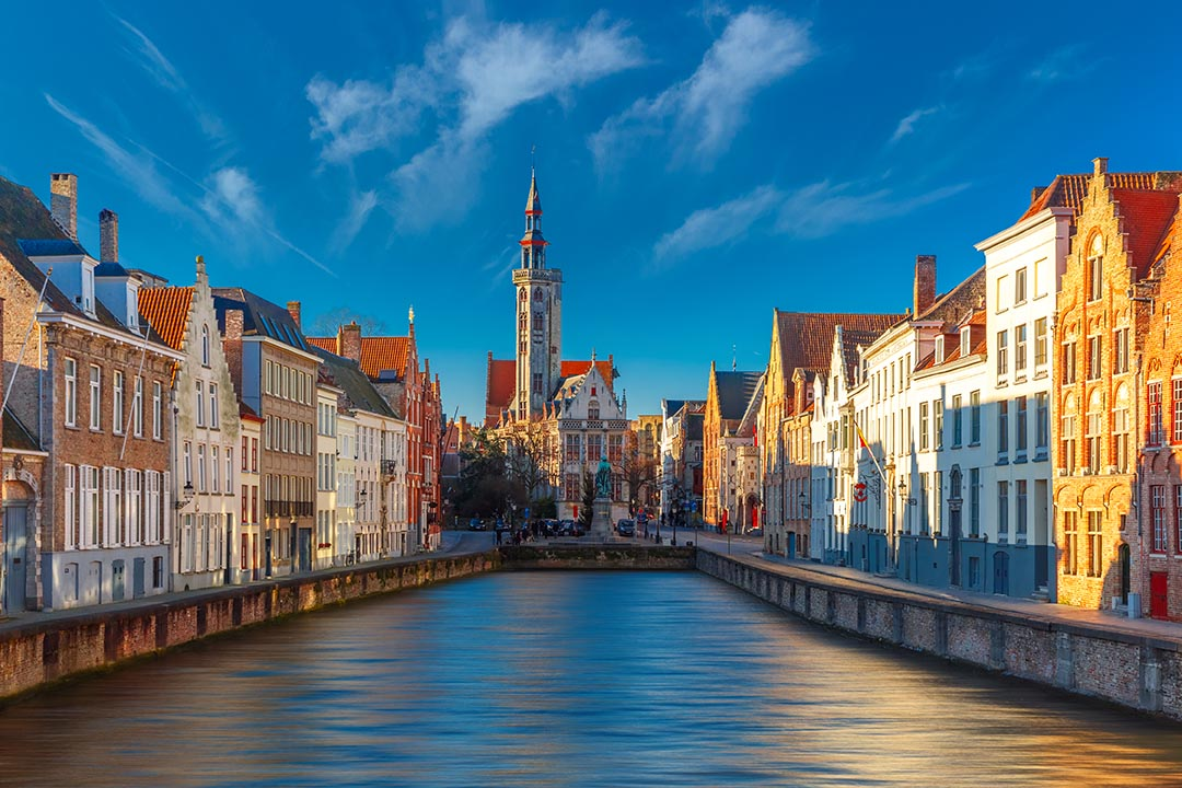 Scenic cityscape with canal Spiegelrei and Jan Van Eyck Square in the morning in Bruges, Belgium. Blue skies in background and canal in the centre with skyline in the middle.