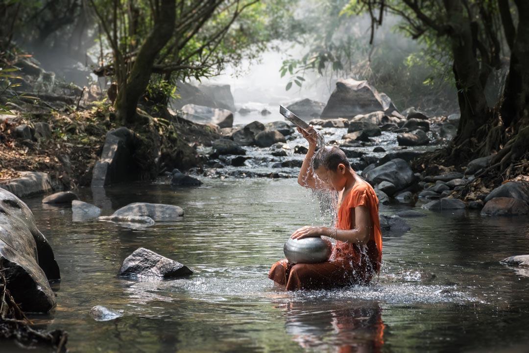 monk in an orange robe sat bathing in a stream