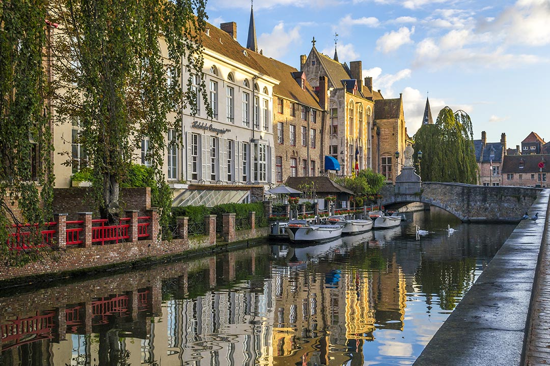 Canal in Bruges with buildings and trees on left hand side.