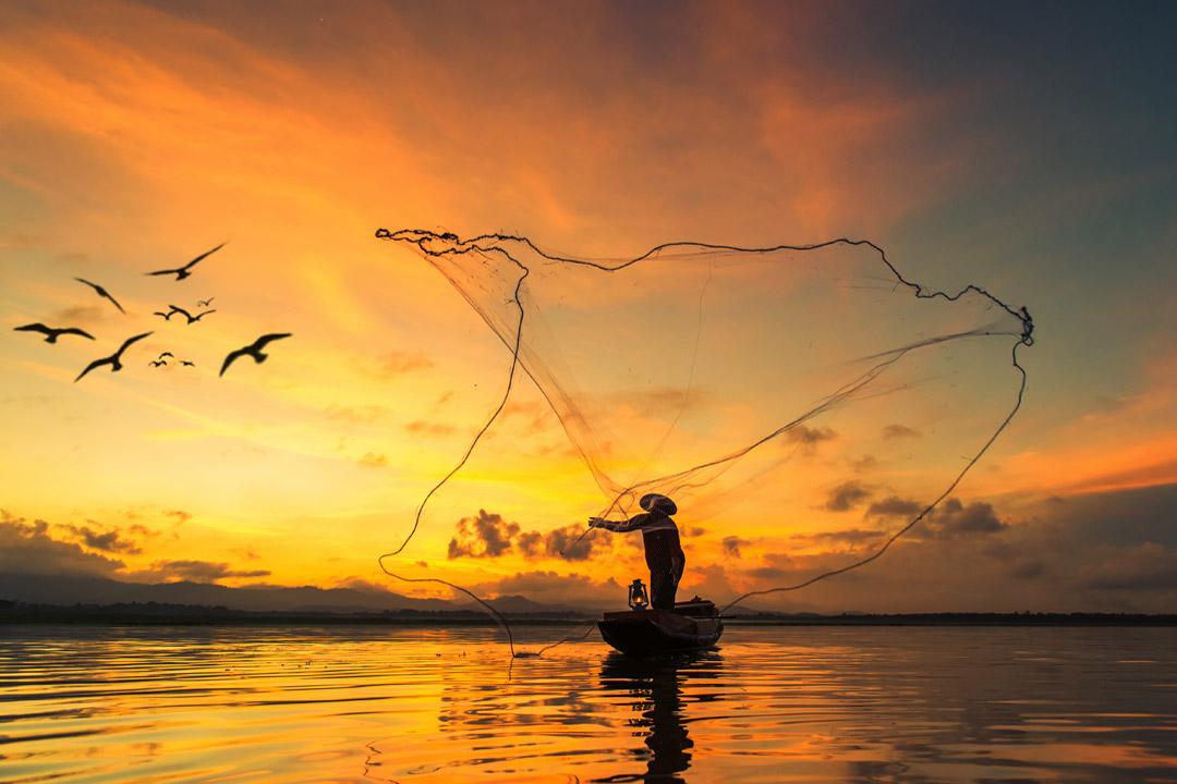 fisherman casting net into sea at sunrise
