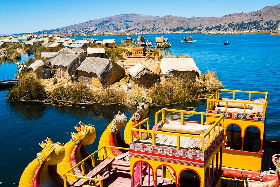 View of Uros floating islands with typical yellow boats on blue water.
