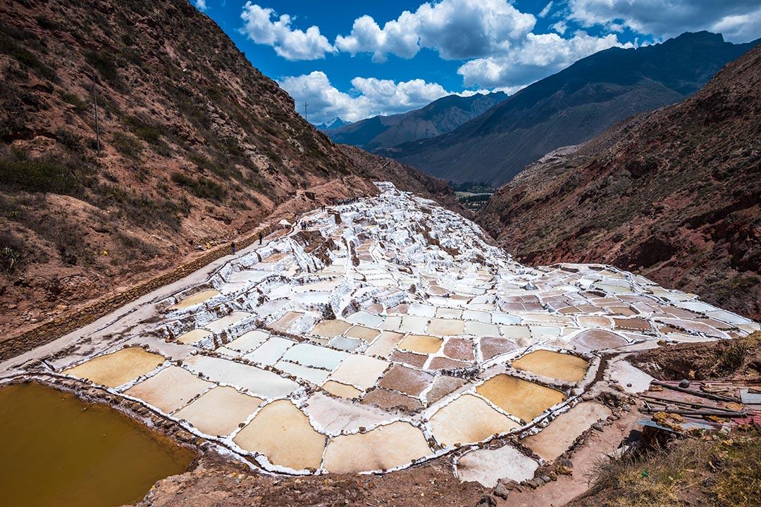 Salinas de Maras, man-made salt mines near Cusco, Peru nestled in between the valley of brown mountains