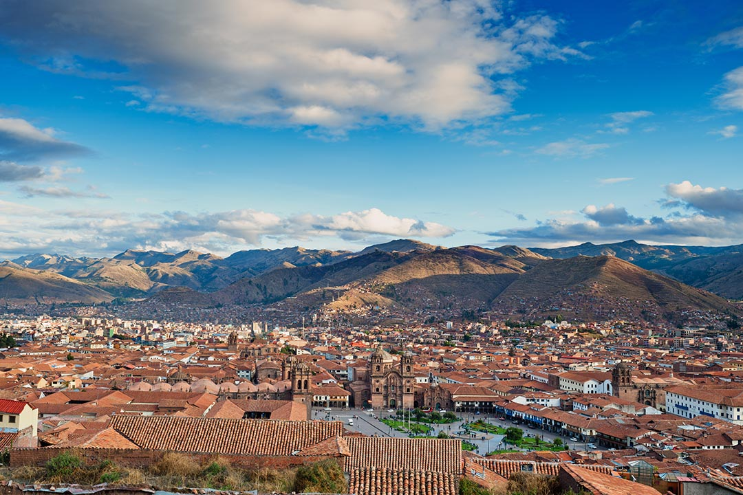 City of Cuzco in Peru, South America with snow topped mountains in the background and city in the foreground.