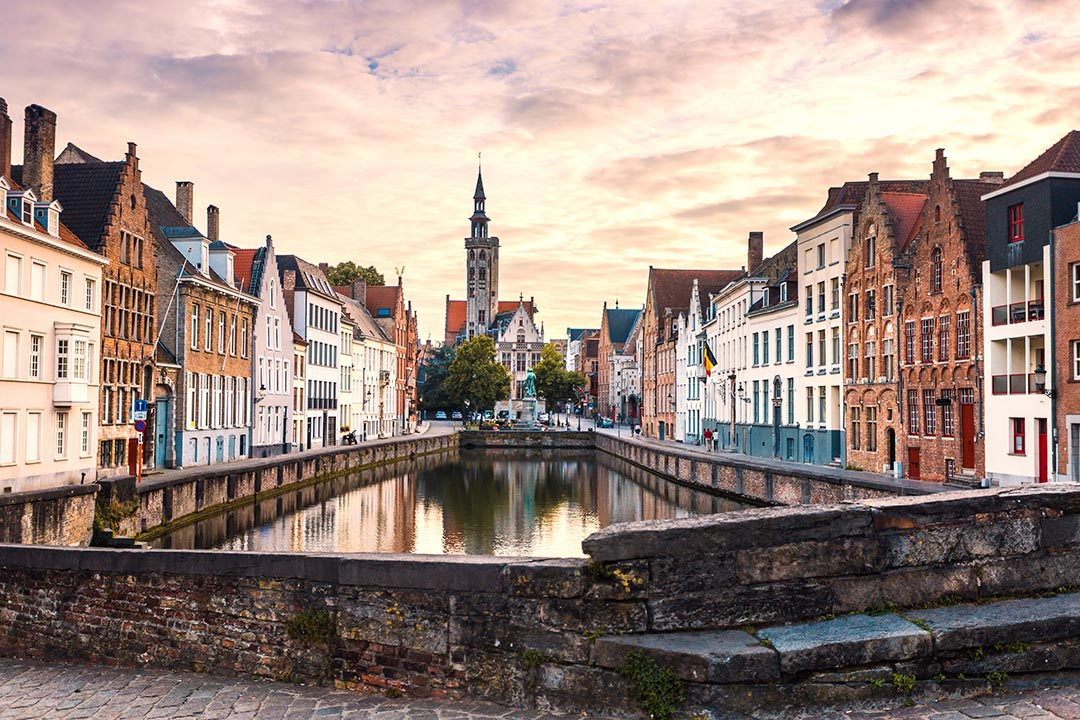 Brugge in evening with colorful sky and old buildings on the edge of the canal which is in the centre of the image.