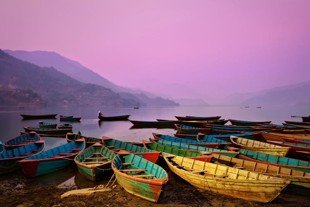 Yellow and green boats on Lake Phewa with purple haze and mountains in the background