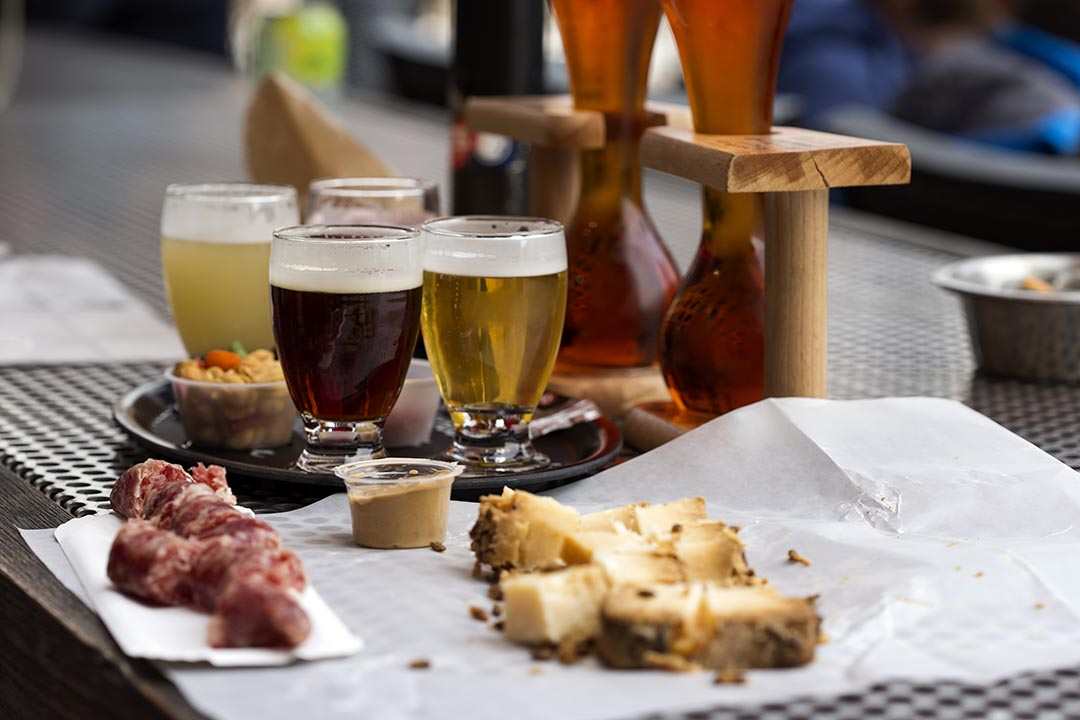 Different types of beer like coconut and cherry beer and cheese with smoked sausage in restaurant