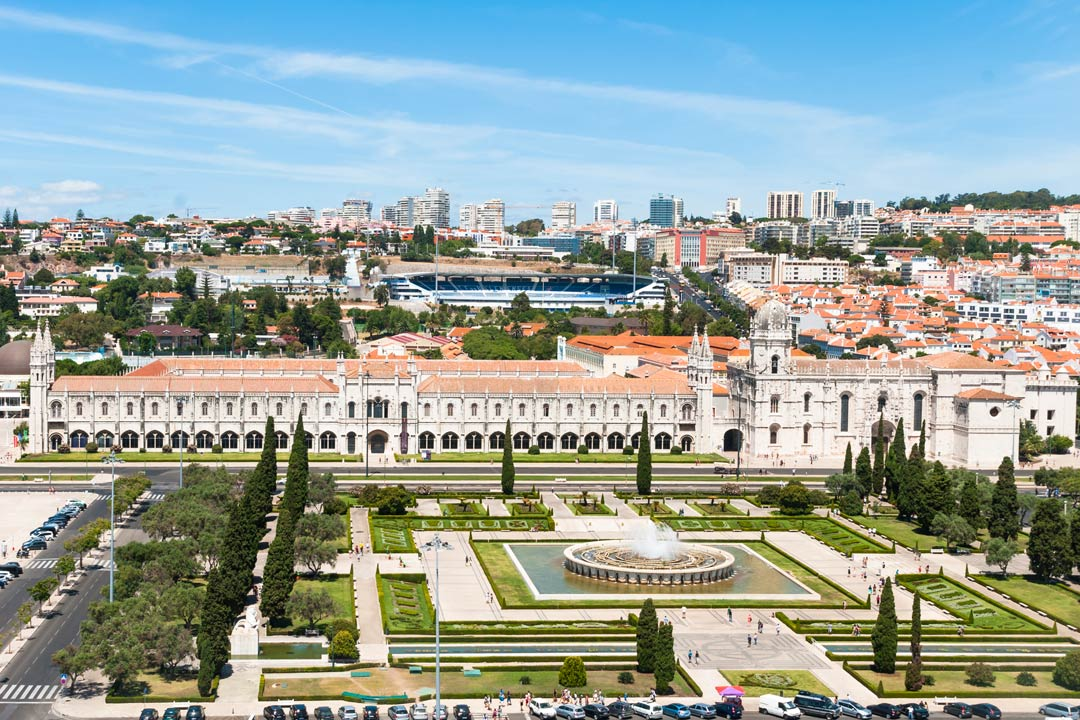 Ornamental square gardens are in front of a palace with many archways. The city sprawls out in the background