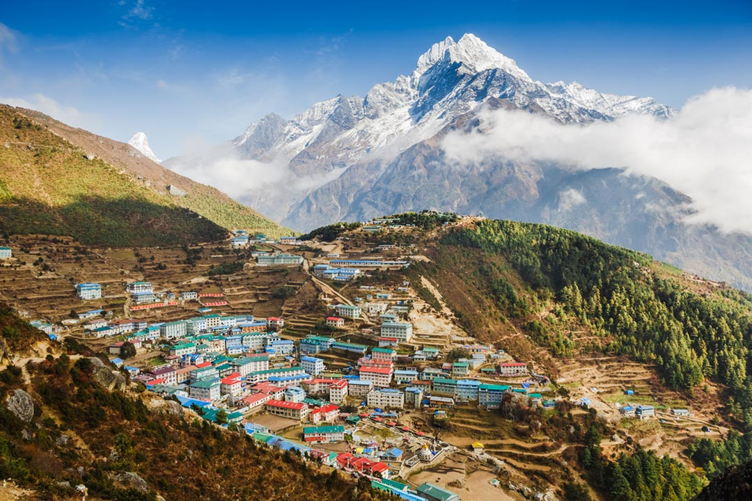 Landscape of Nepal with snow topped mountain in the background and houses in the hilly valley below.
