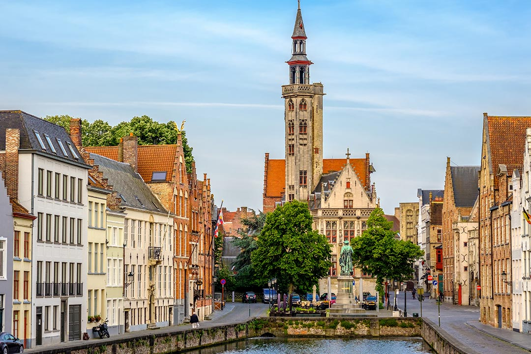 Cityscape of Bruges with old buildings with terracotta roofs and canal in foreground.