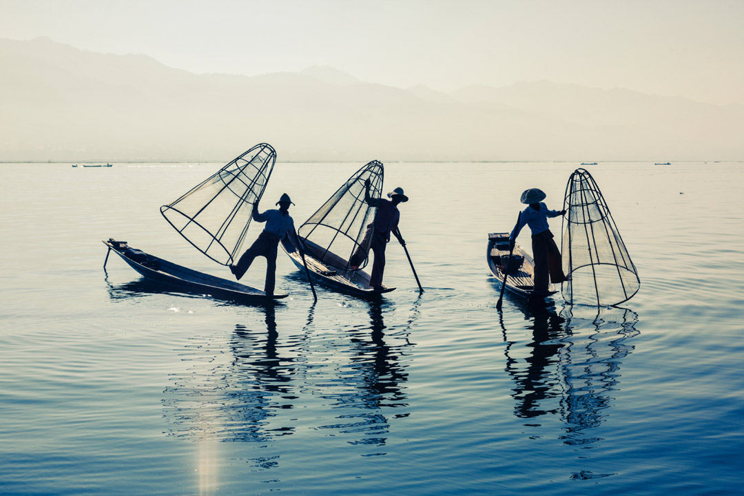 fishermen standing on a boat on one leg trying to make their catch of the day