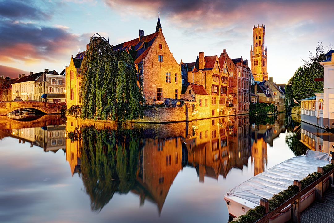 Old buildings and Belfort van Brugge next to canal at sunset.