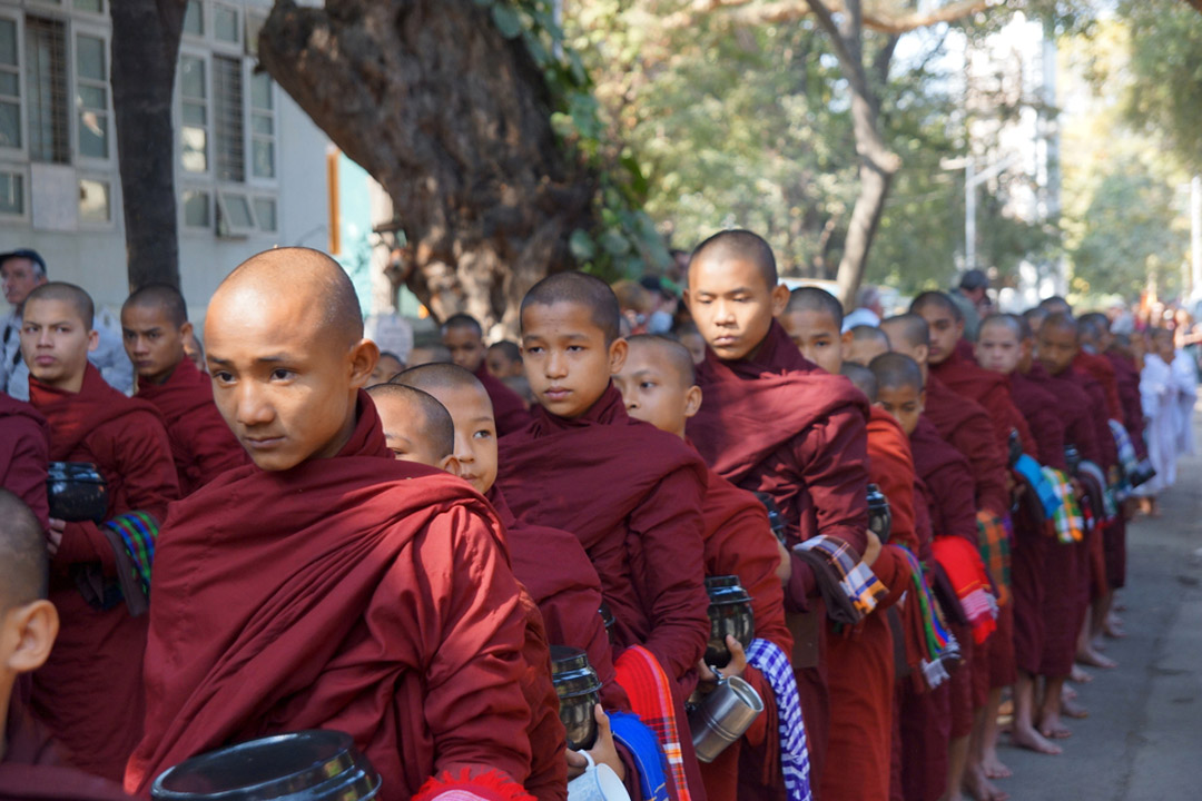 monks in maroon robes lining up outside monastery
