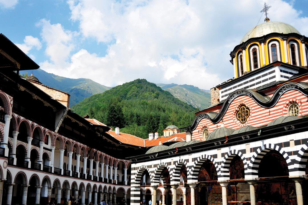 The ornate arches of a building against the backdrop of rugged and imposing mountains