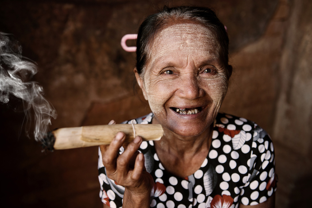 older woman smiling at camera holding a cigar