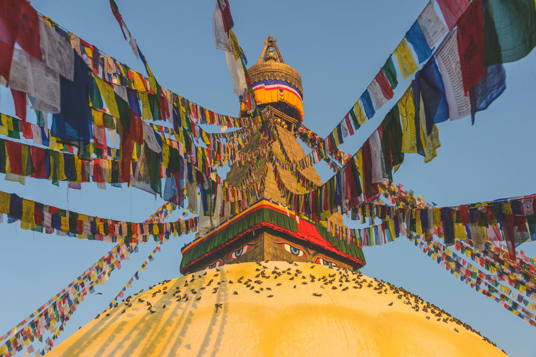 Red, blue, yellow, green and white prayer flags draping off the gold top of a stupa