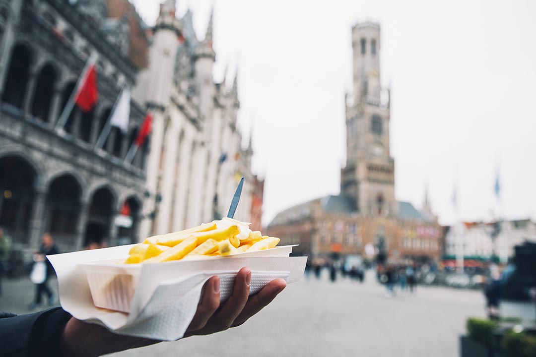 Tourist holds in hand popular street junk food - French Fries with mayonnaise.