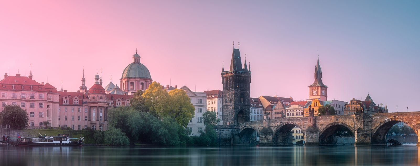 Morning view of Charles bridge and Prague cityscape with sunbeams, Czech Republic. Travel concept background.