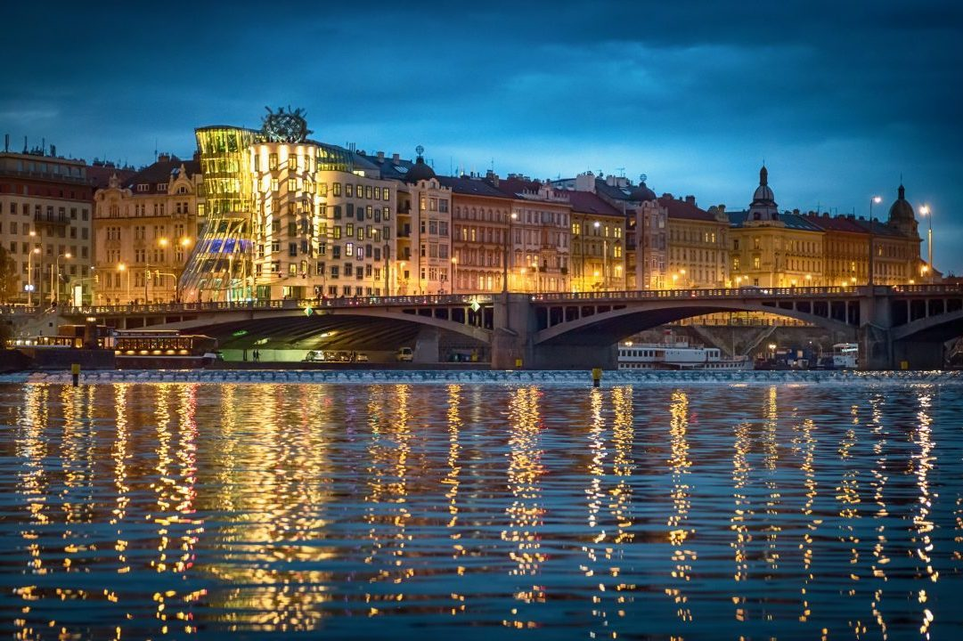 Dancing house in Prague at night reflected in the Vltava river. Pragua, Czech Republic.