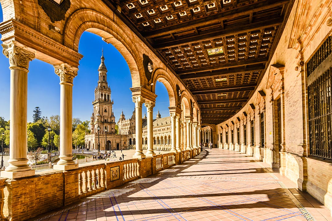 A sweeping covered walkway at the Plaza de Espana. Golden stone is lit up in the sunshine with blue sky appearing in between the arches of the walkway.