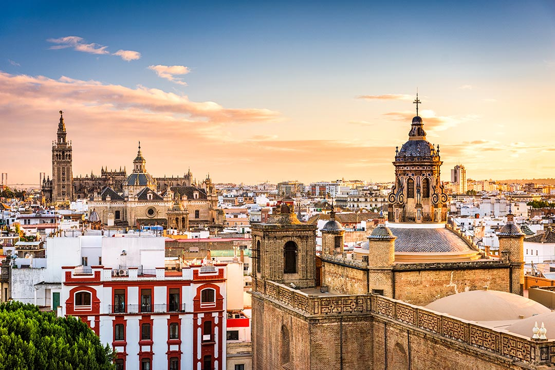a view of Seville's skyline with a red and white building in the foreground