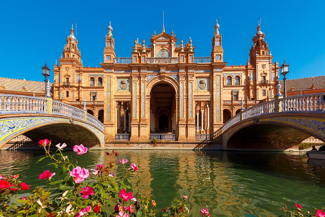 A straight on view of Plaza de Espana in Seville with bridges on the left and right and an ornate building with blue sky in the background. Water and pink and red flowers are in the foreground.