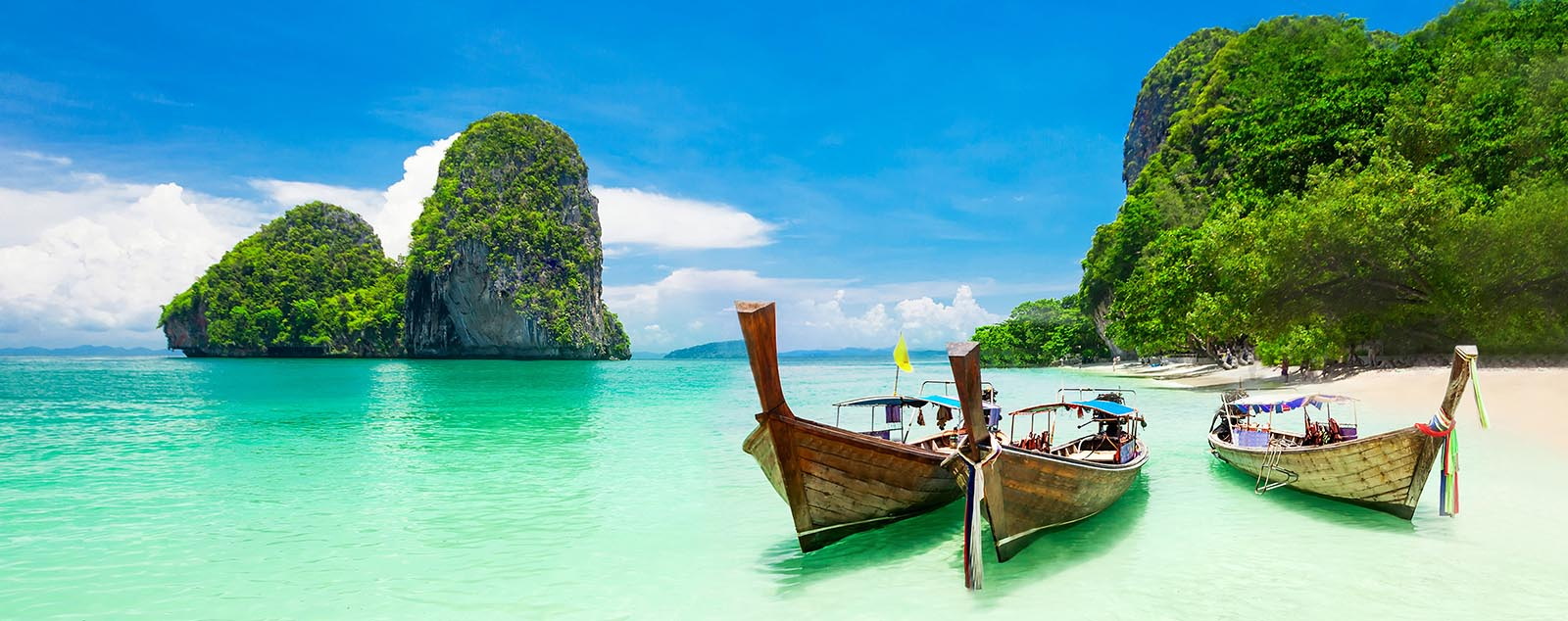three longtail boats on turquoise water docked at a white sand beach with greenery and limestone cliffs in the background