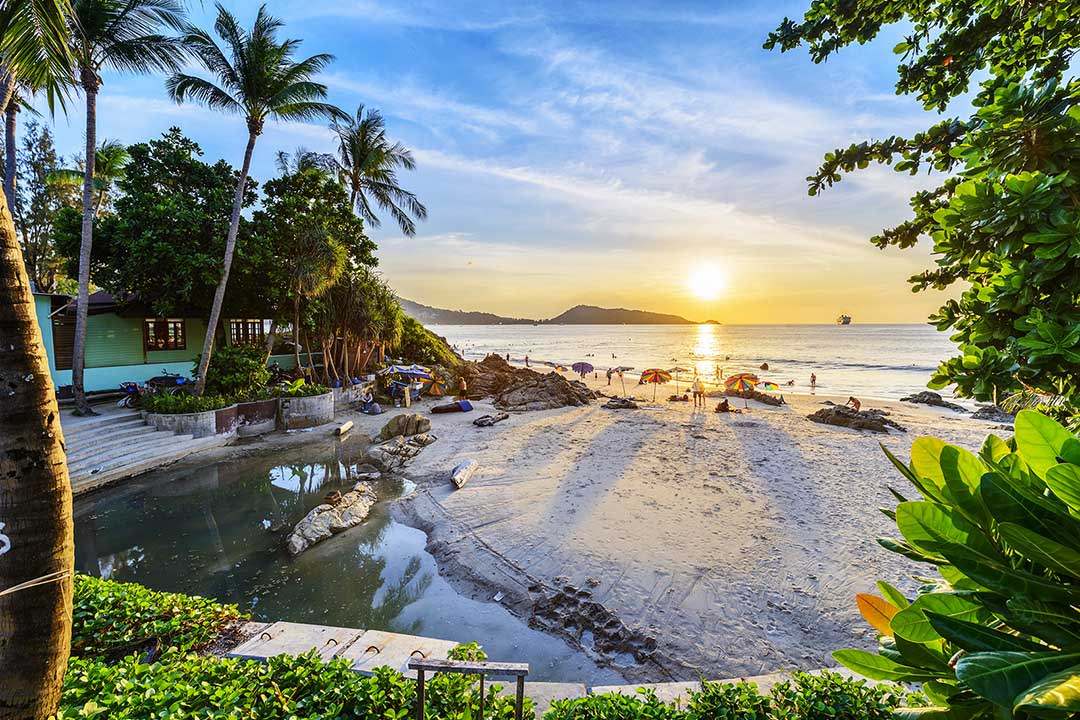 A beach cove surrounded by lush greenery, palm trees, at sunset.