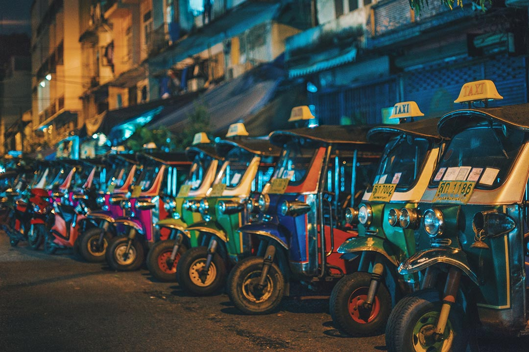 Brightly coloured Tuk Tuk's lined up together on a street.