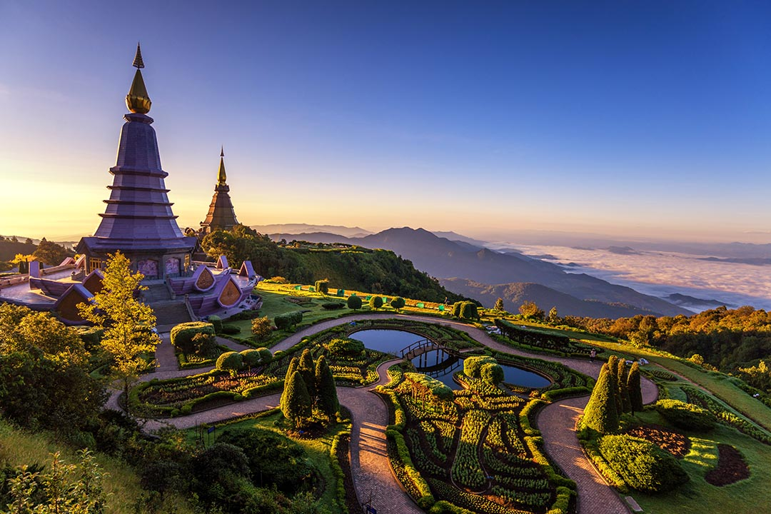 Towering temple on a hillside in Chiang Mai looking over landscaped lakes and green valley with clouds between the hills