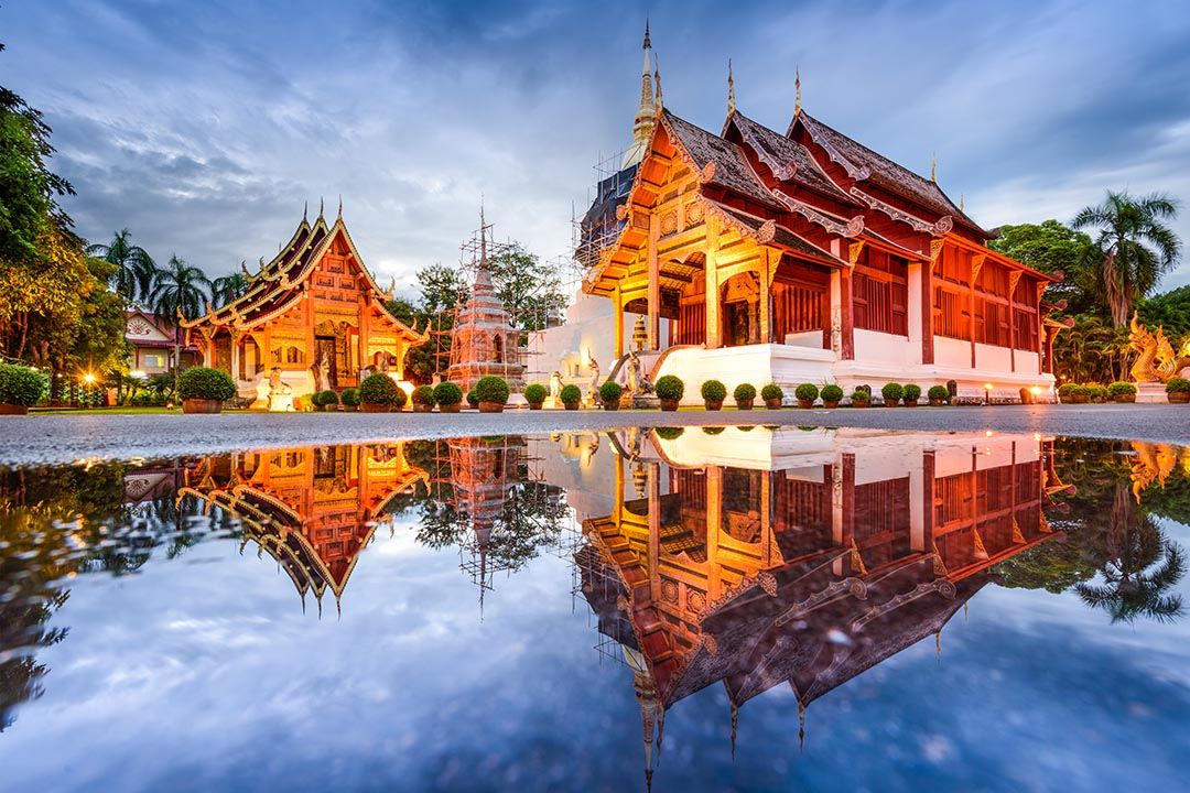 Wat Phra Singh temple in Chiang Mai, two gold and temples lit up against a twilight sky