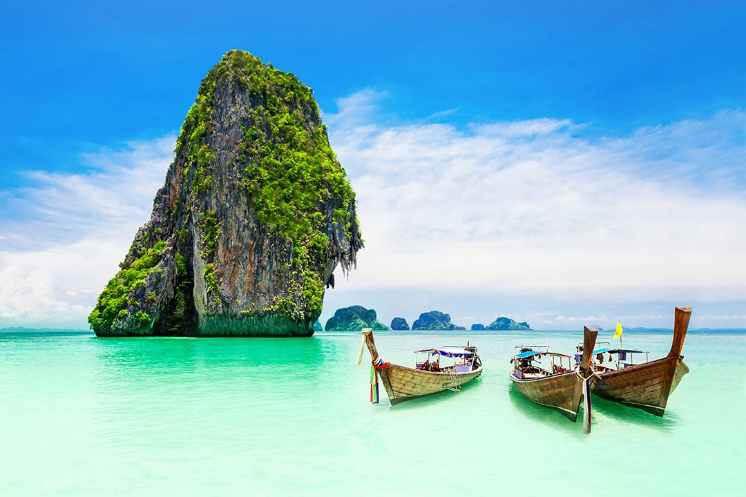 Three longtail boats on turquoise water with limestone rock protruding out of the water in the background.