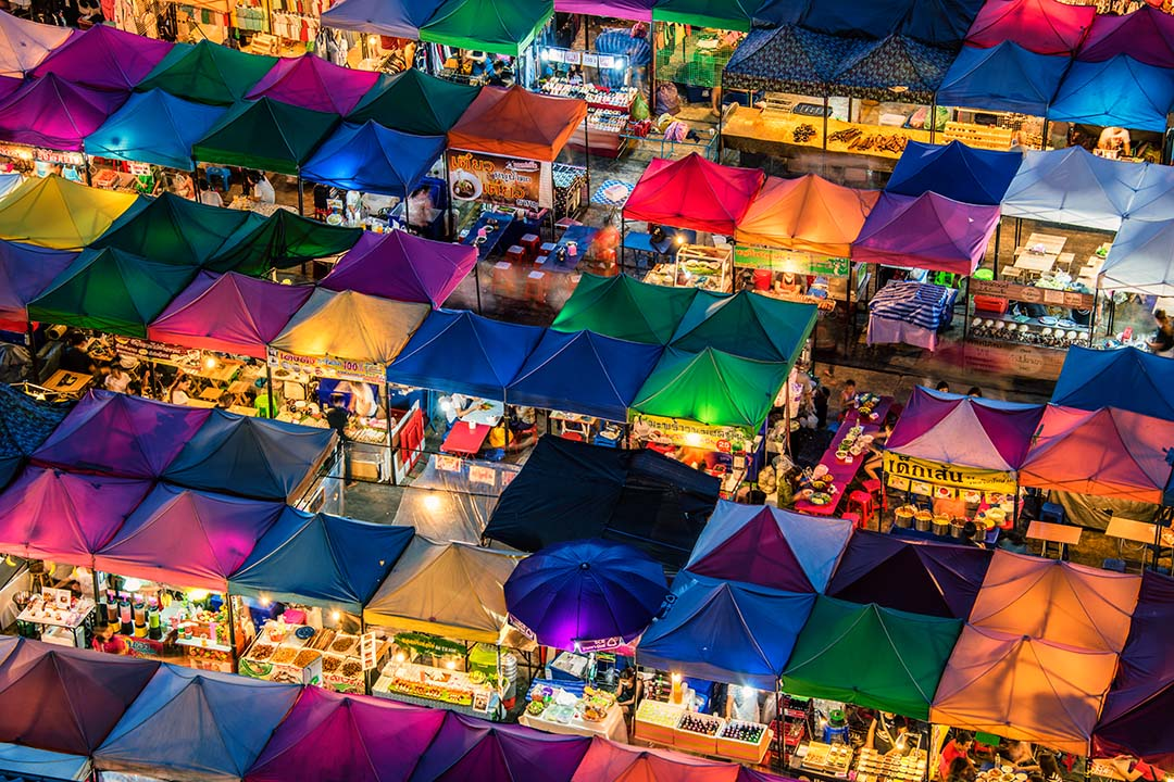 An aerial view of a night market; rows of multicoloured tents are lined closely together