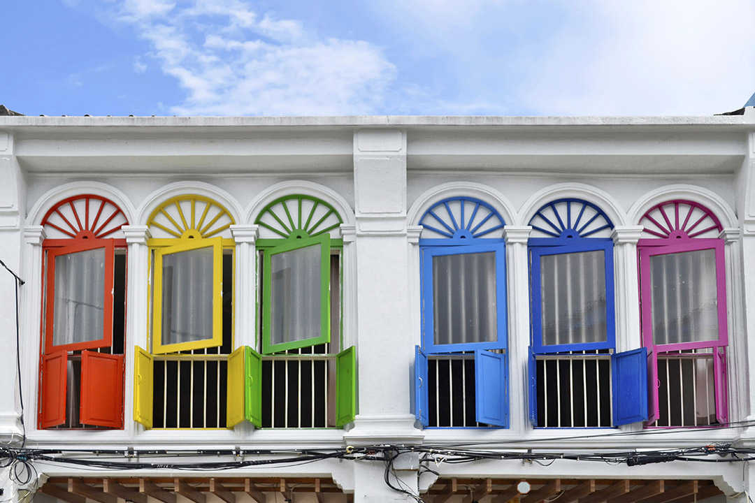 Coloured window frames juxtaposed by a white washed building, in the Sino-Portuguese part of Phuket