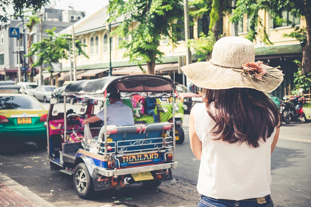 Girl taking photo of a blue three wheeled tuk tuk on a busy street in Thailand