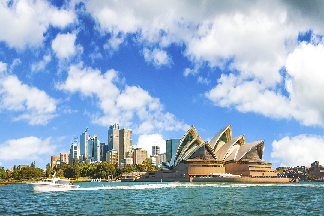 A view of Sydney Opera House on a blue day, from the water.