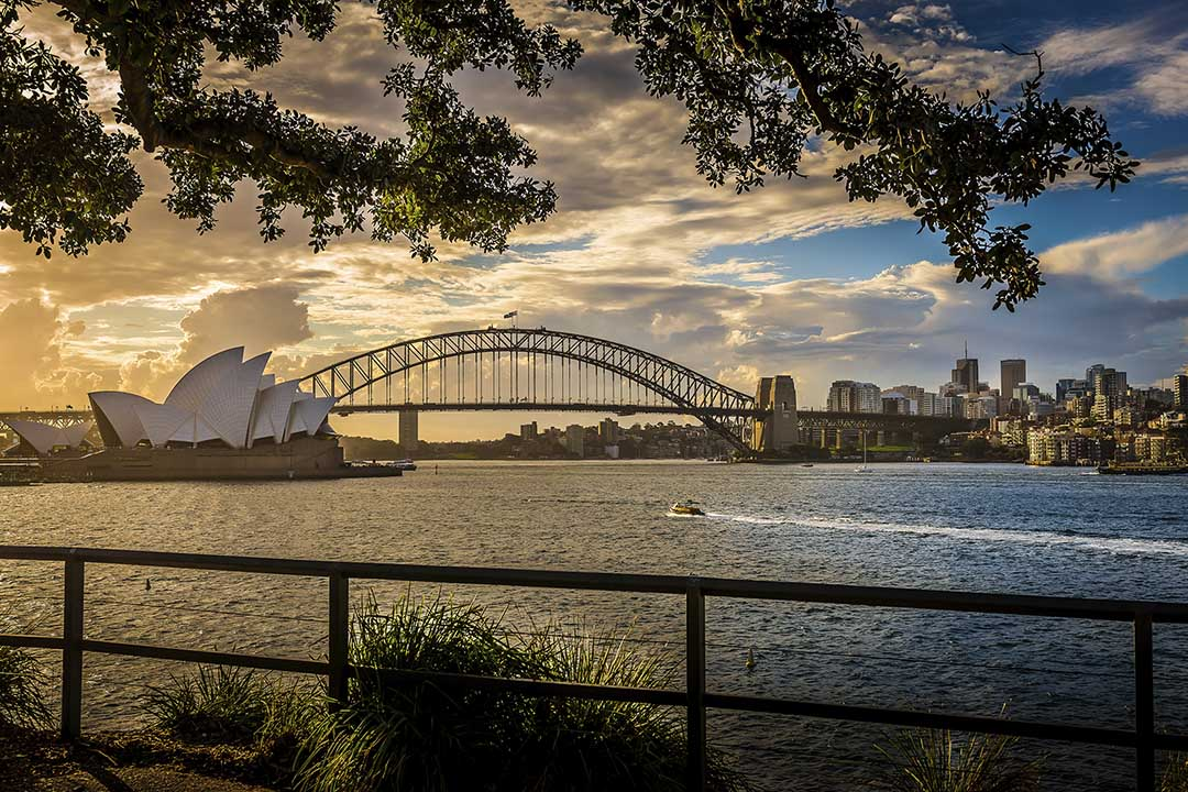 Sydney Harbour Bridge and the Opera House in the distance, in a beautiful dusky sky.