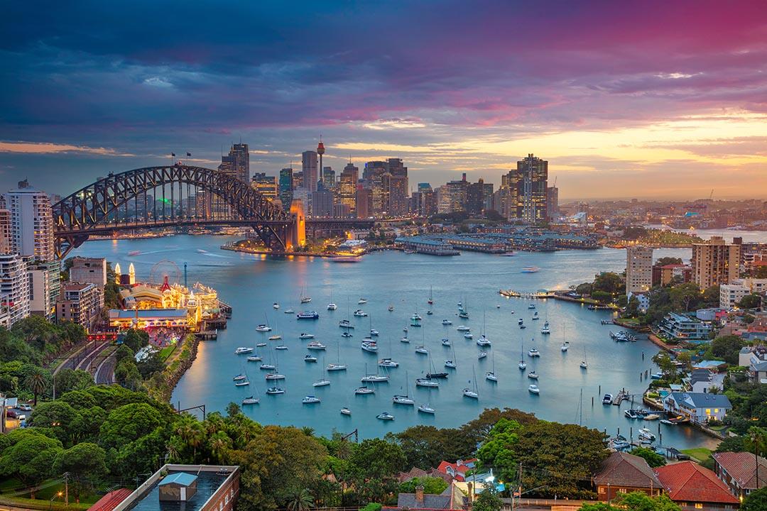 Cityscape image of Sydney, Australia with Harbour Bridge and Sydney skyline during sunset.